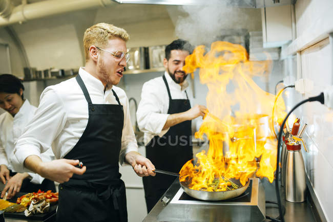 Happy cook making a flambe in restaurant kitchen with colleague watching — Stock Photo
