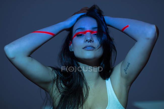 Mujer atractiva joven con línea roja en la cara y los brazos sobre fondo oscuro - foto de stock