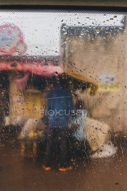 Ethnic person standing on village street in rainy day — Stock Photo