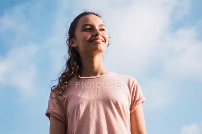 Menina adolescente em pé na frente do céu azul com nuvens — Fotografia de Stock
