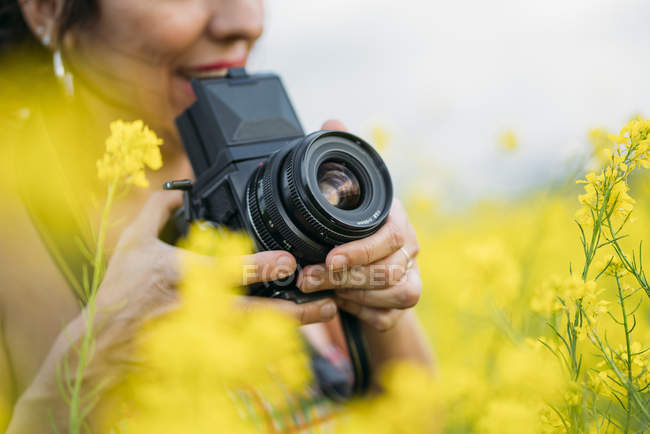 Закри жінка з ретро фотоапарат фотографують в природі з жовтими квітами — стокове фото