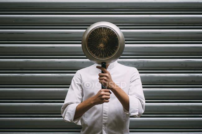 Homem, cobrindo o rosto com frigideira contra a parede do metal — Fotografia de Stock