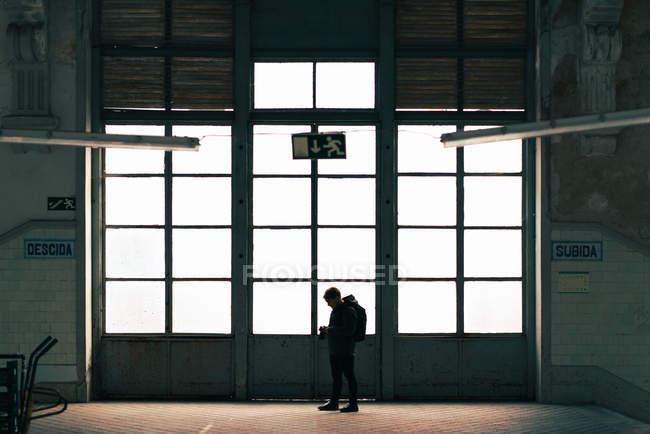 Männliche Touristen stehen auf große leichte Tür im Gebäude mit Kamera — Stockfoto