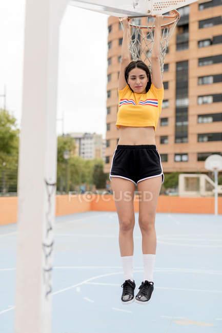 Magro mulher no sportswear pendurado no basquete aro ao ar livre na cidade — Fotografia de Stock