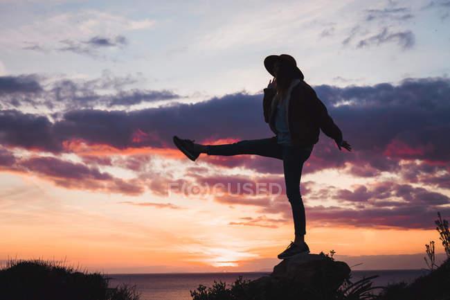 Жінка в капелюсі стоячи на узбережжі під вечір небо — стокове фото