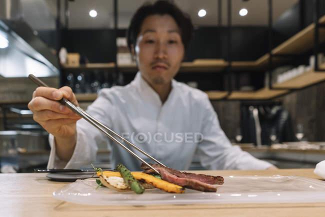 Шеф-повар готовит блюдо с палочками для еды в ресторане — стоковое фото