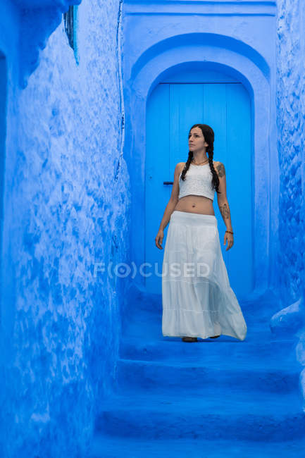 Woman wearing white top and long skirt standing on blue dyed street, Morocco — Stock Photo
