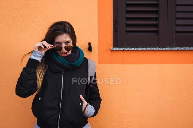 Взволнованная женщина, снимая очки против строительства — стоковое фото