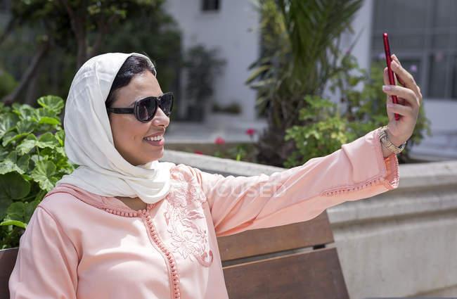 Marokkanerin mit Hijab und typische arabische Kleidung nehmen Selfie im freien — Stockfoto