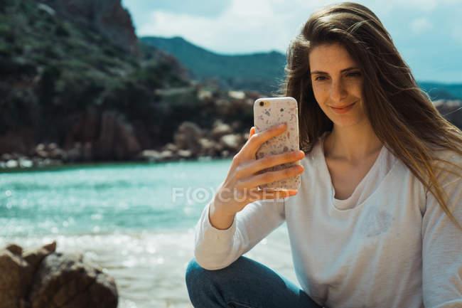 Frau macht Selfie mit Smartphone am felsigen Meer — Stockfoto