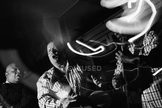 Кубинское музыкальное трио, действующее в ночном клубе, черно-белый кадр с длительной экспозицией — стоковое фото