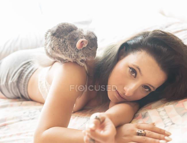 Молодая женщина лежит в постели с шиншиллой на плече — стоковое фото