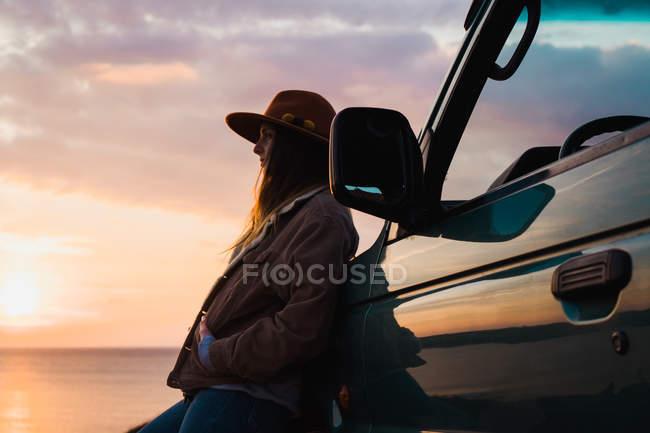 Продуманий жінка, спираючись на автомобіль на узбережжі моря, на заході сонця — стокове фото