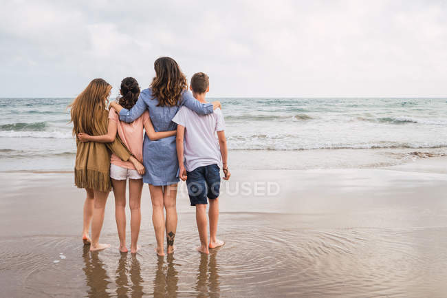Woman and teenagers hugging together on seashore — Stock Photo