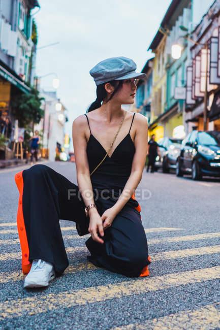 Jovem mulher asiática sentado no joelho na estrada na cidade e olhando para longe — Fotografia de Stock