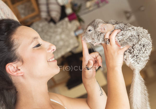 Young smiling woman playing with chinchilla — Stock Photo
