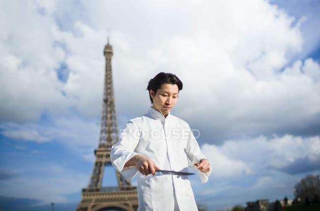 Japanischer Koch mit Messern vor dem Eiffelturm in Paris — Stockfoto