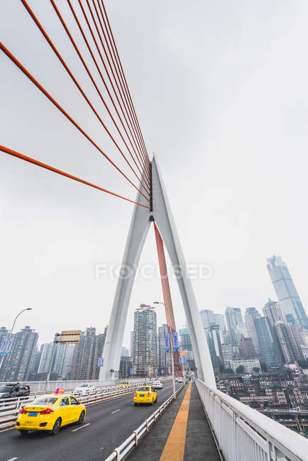 Modern suspension bridge construction with cars driving on background of metropolis of Chongqing, China — Stock Photo