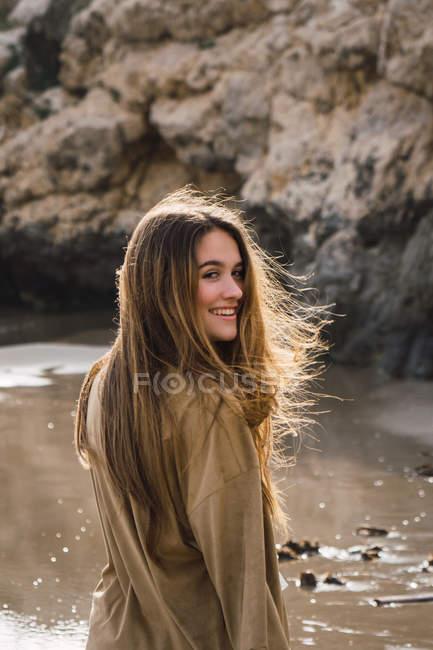 Ritratto di ragazza con lunghi capelli castani in piedi sulla spiaggia — Foto stock