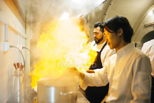 Cook making flambe in restaurant kitchen — Stock Photo
