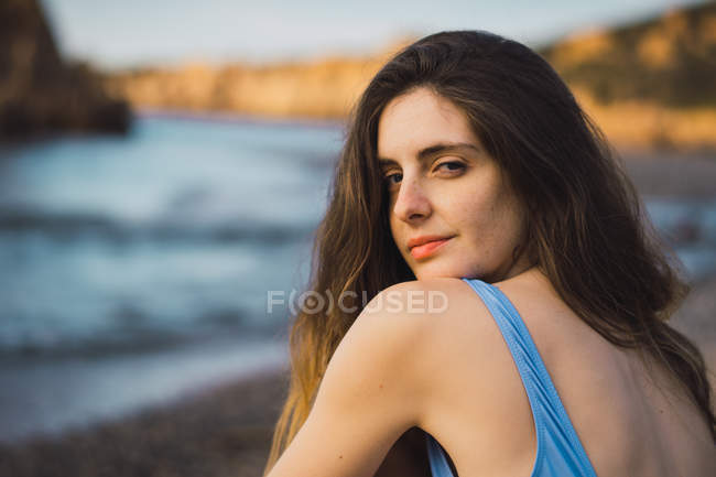 Portrait of young woman in swimsuit sitting on beach — Stock Photo
