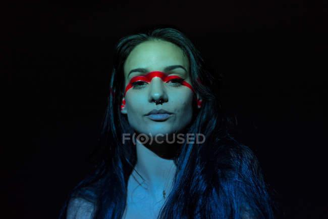 Молодая привлекательная женщина с красной линией на лице смотрит в камеру на черном фоне — стоковое фото