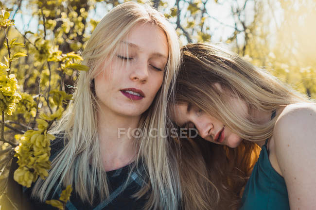 Dreaming tender girls embracing in nature with closed eyes — Stock Photo