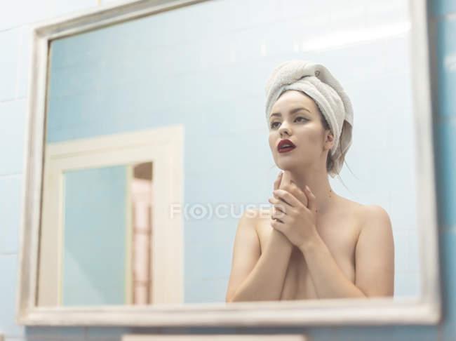 Giovane donna in topless con trucco e asciugamano sulla testa in piedi davanti allo specchio in bagno — Foto stock