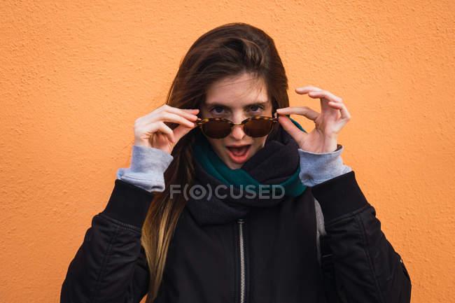 Взволнованная женщина, снимая очки оранжевый стену — стоковое фото