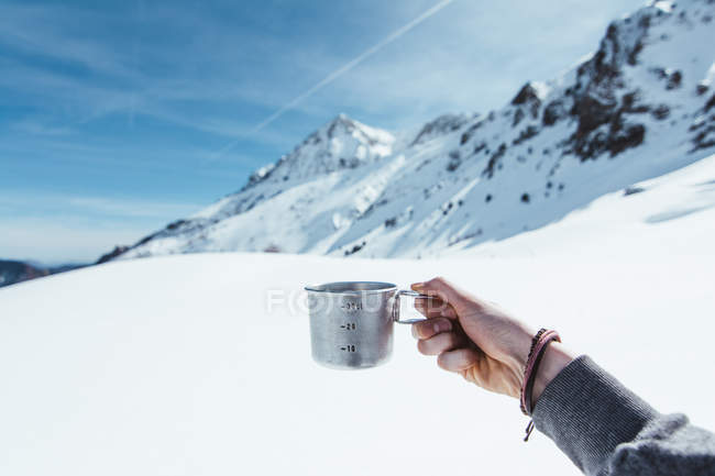 Hand of unrecognizable tourist holding metal cup in mountains in winter — Stock Photo