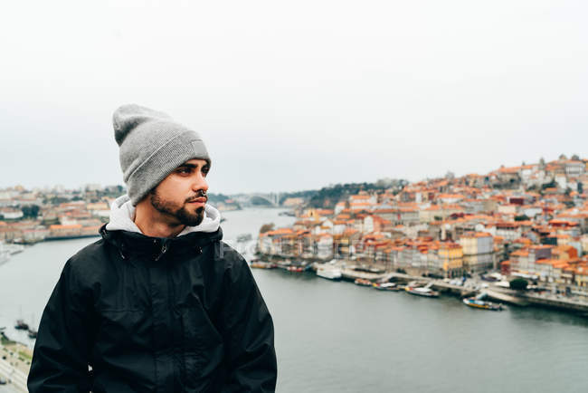 Young man standing in front of old city with orange roofs, Porto, Portugal — Stock Photo