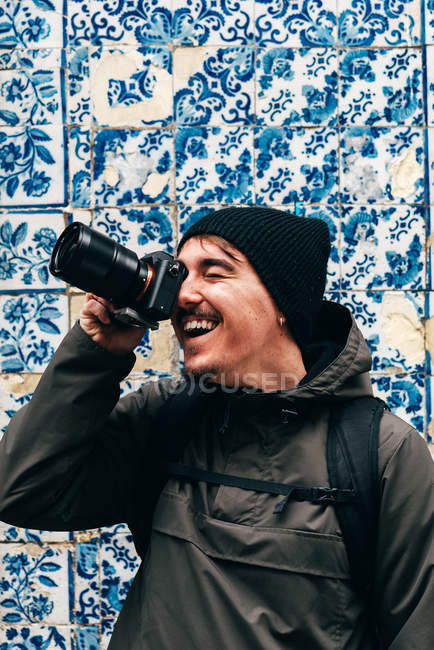 Cheerful male tourist standing at wall with blue tiles and taking photo — Stock Photo