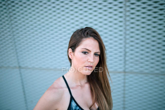 Portrait of young woman in sports clothes standing in front of net — Stock Photo