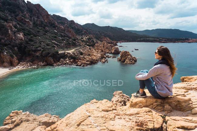 Туристична жінка, сидячи на скелі і, дивлячись на bay — стокове фото