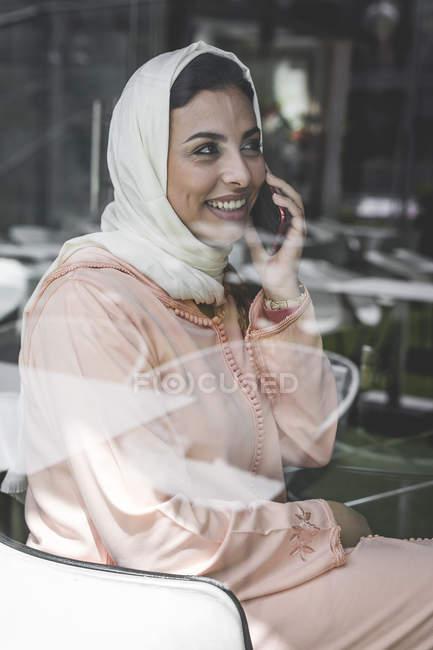 Vestido de mulher marroquina com hijab e tradicional árabe falando no telefone por trás do vidro da janela — Fotografia de Stock