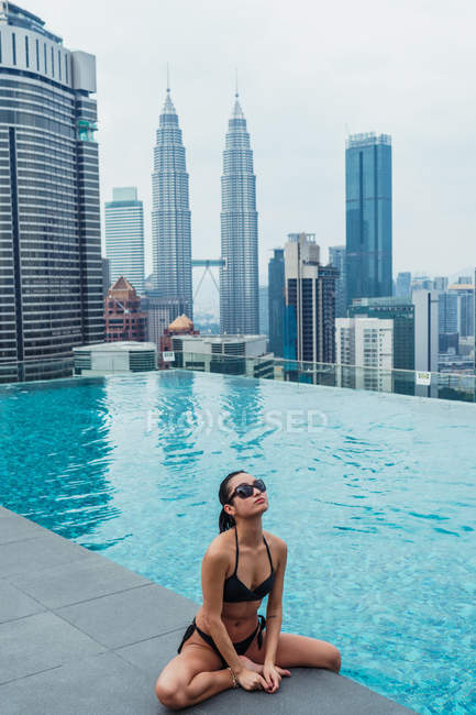 Asiática relajada mujer sentado en la piscina con rascacielos en el fondo - foto de stock