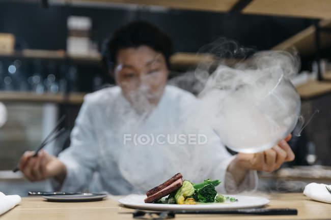 Шеф-повар, приготовление пищи в ресторане с дым блюдо — стоковое фото