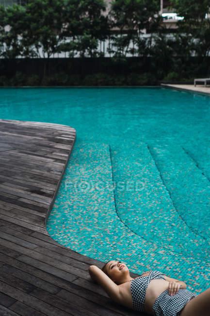 Усміхається жінка розслабляючий на дерев'яну підлогу біля басейну — стокове фото