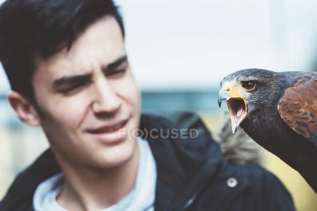 Nahaufnahme eines Mannes, der einen Falken auf der Hand sieht — Stockfoto