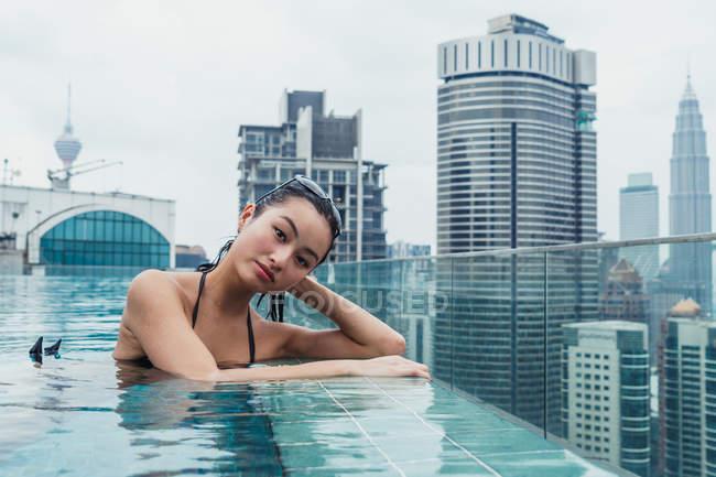 Ritratto di donna asiatica rilassante in piscina con moderni grattacieli sullo sfondo — Foto stock