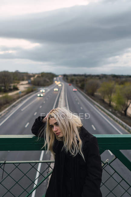 Thoughtful blonde woman standing at fence on bridge over road — Stock Photo