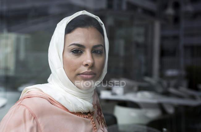 Продуманий Марокканський жінка з хіджаб дивлячись камера позаду області вікна — стокове фото