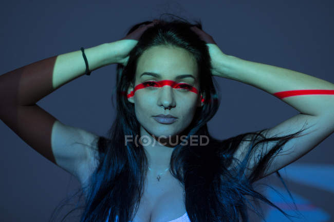 Young attractive woman with red line on face and arm on dark background — Stock Photo
