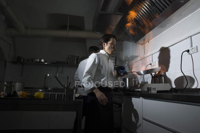 Cook making a flambe in restaurant kitchen with colleague on background — Stock Photo