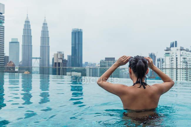 Азіатський жінка розслабляючий в басейн з видом на місто на тлі — стокове фото