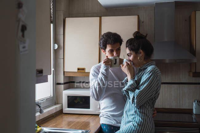 Молода пара в піжамі, пити з чашки кухні — стокове фото
