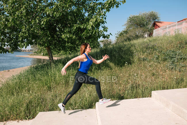 Young woman running outdoors next to lake — Stock Photo