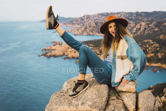 Portrait of stylish cheerful woman in hat sitting on rock at ocean — Stock Photo