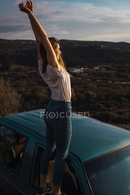 Женщина, стоящая на окне автомобиля с поднятыми руками в природе — стоковое фото