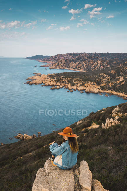 Woman on rock at ocean and looking away — Stock Photo